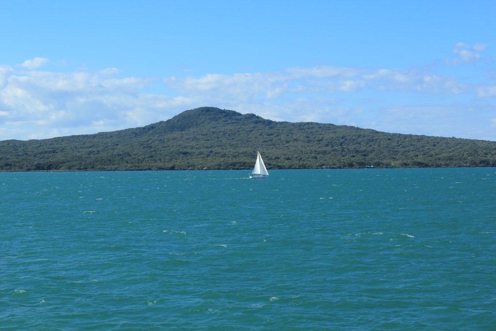 Voilier dans la baie d'Auckland et l'île volcanique de Rangitoto